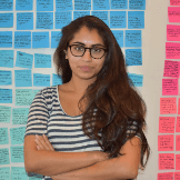 Puja Balachander headshot, with post-it notes on the wall