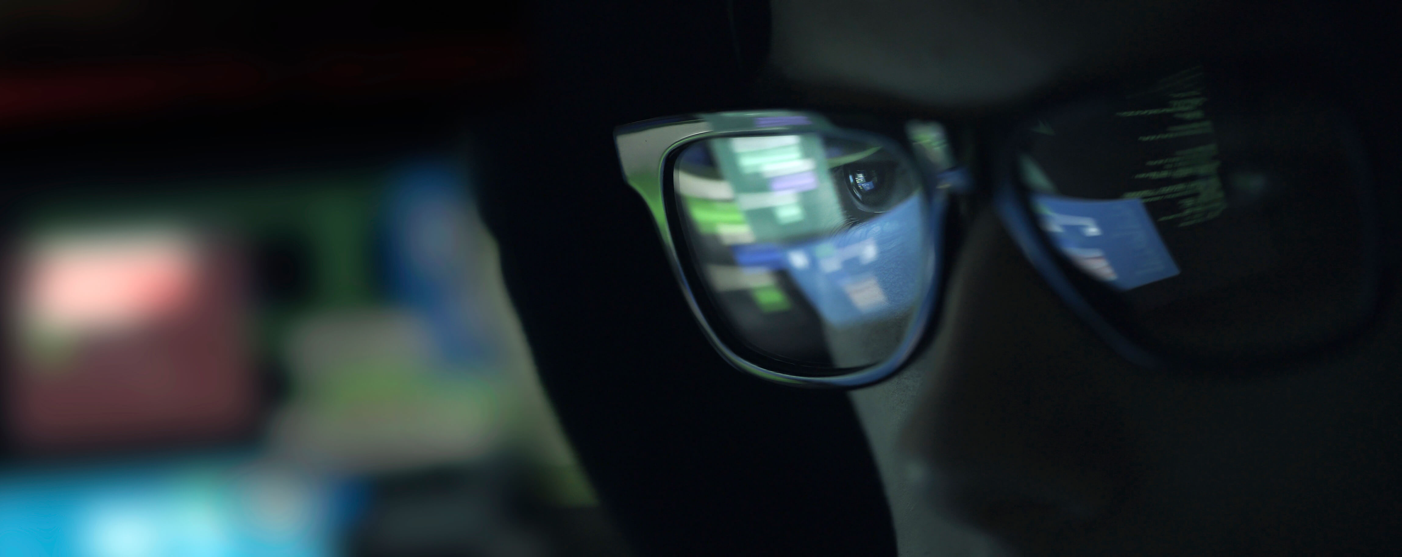 Reflection in glasses of person looking at screen