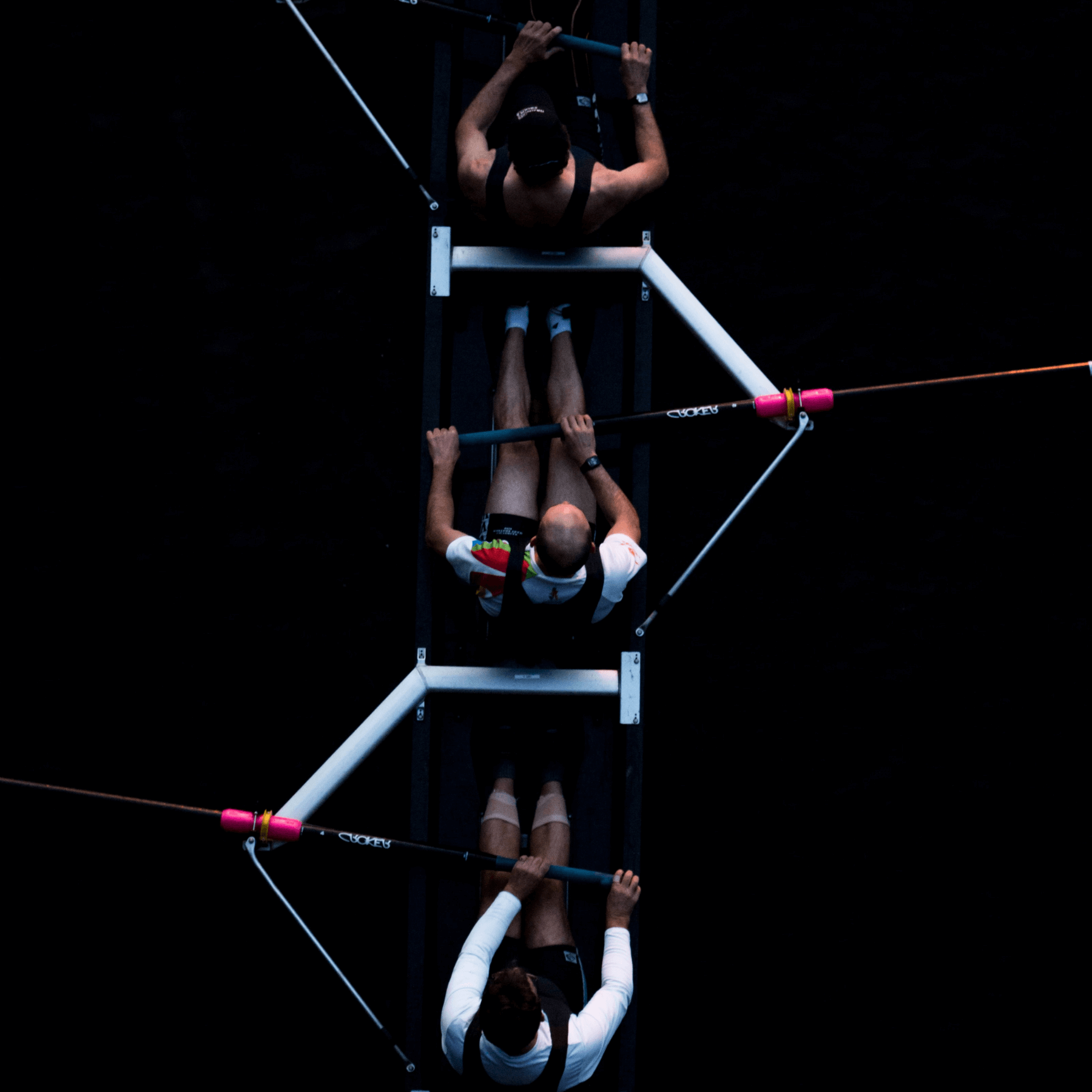 Three people rowing with black background