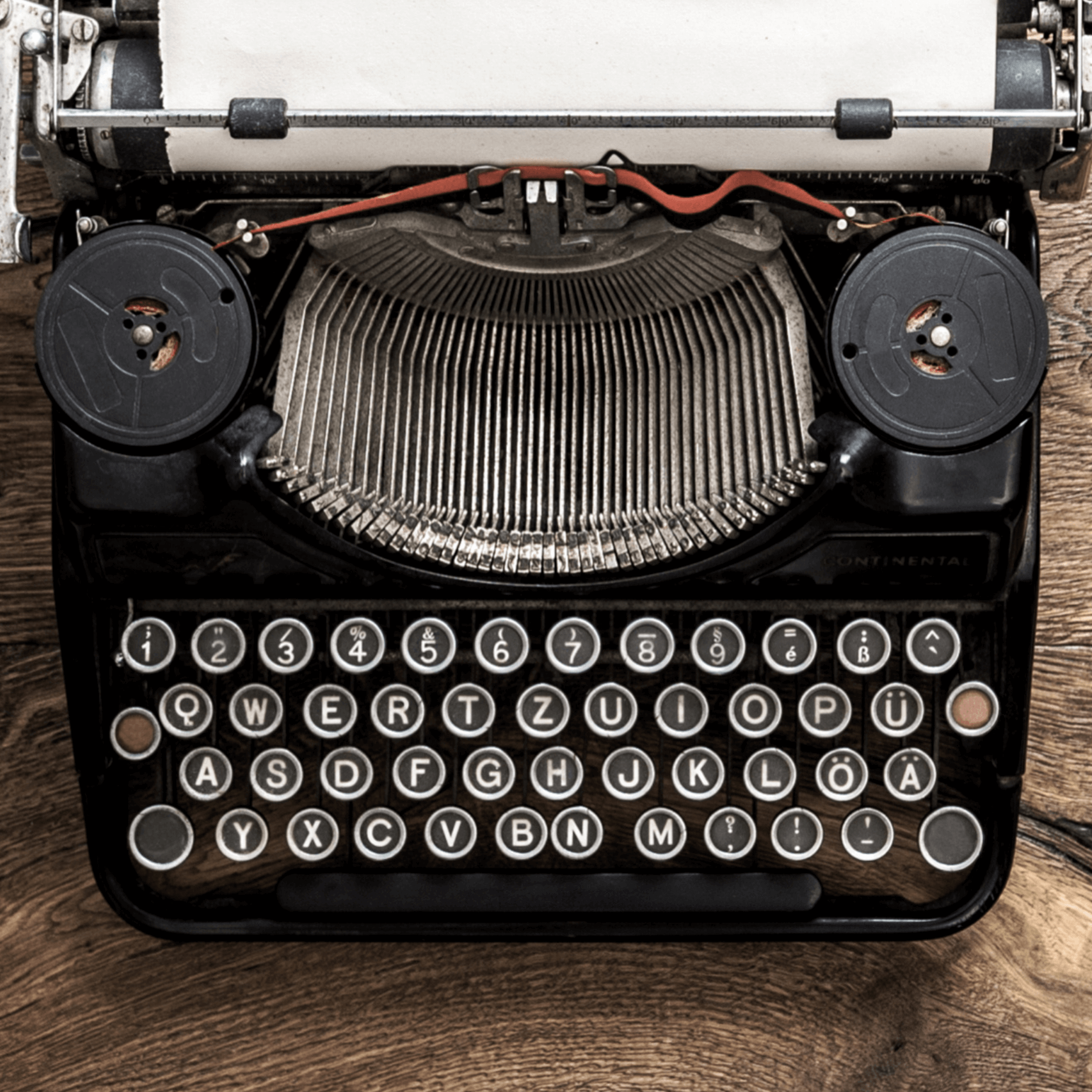 Black Typewriter with blank white paper on wooden table
