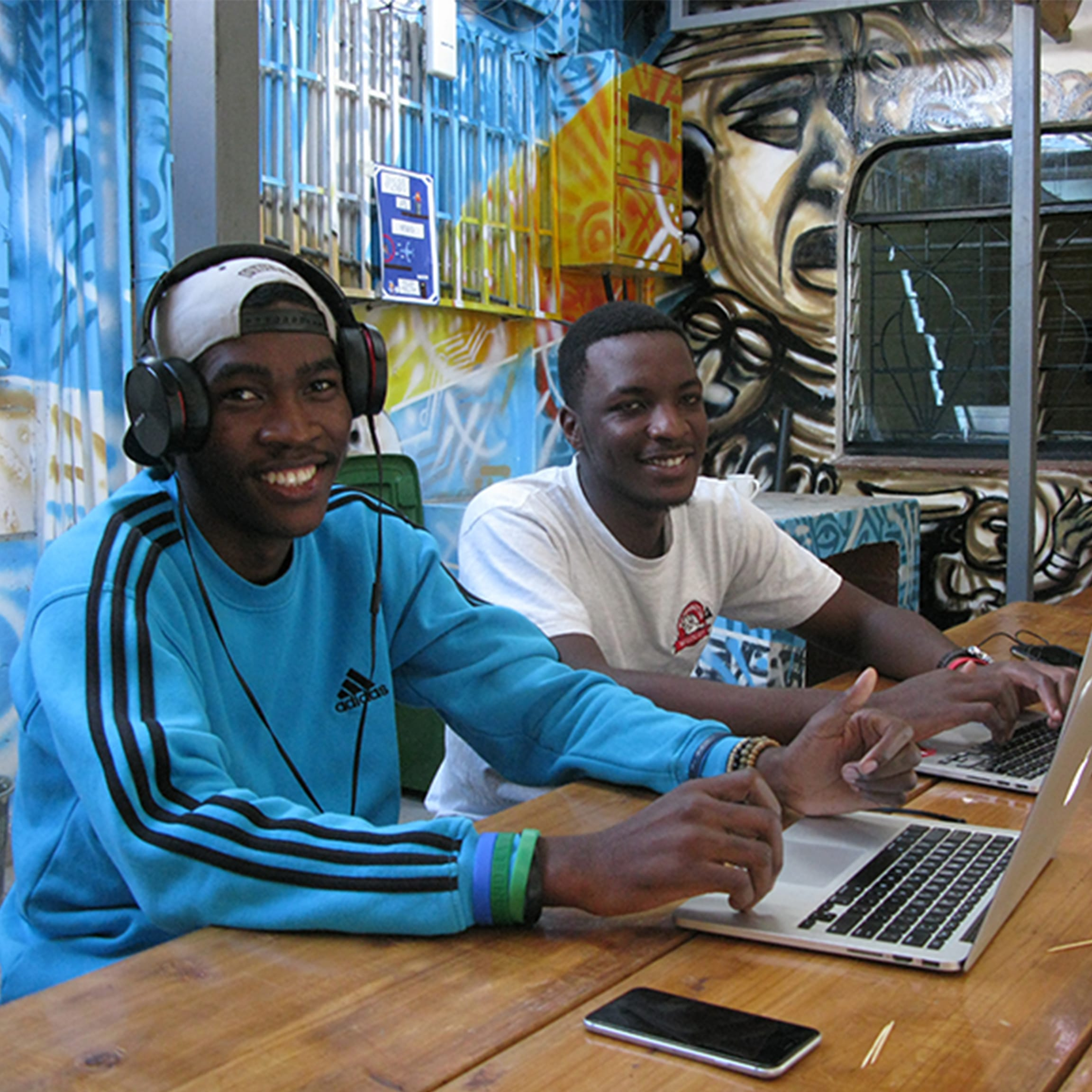 Two young men sat with laptops