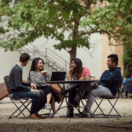 mba students sitting at table in leafy quad