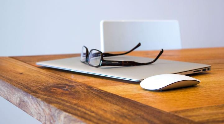 Desk with laptop and glasses