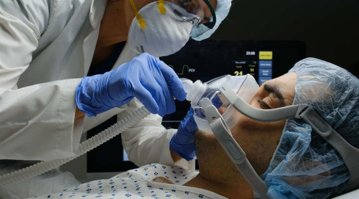A doctor treating a patient on a ventilator