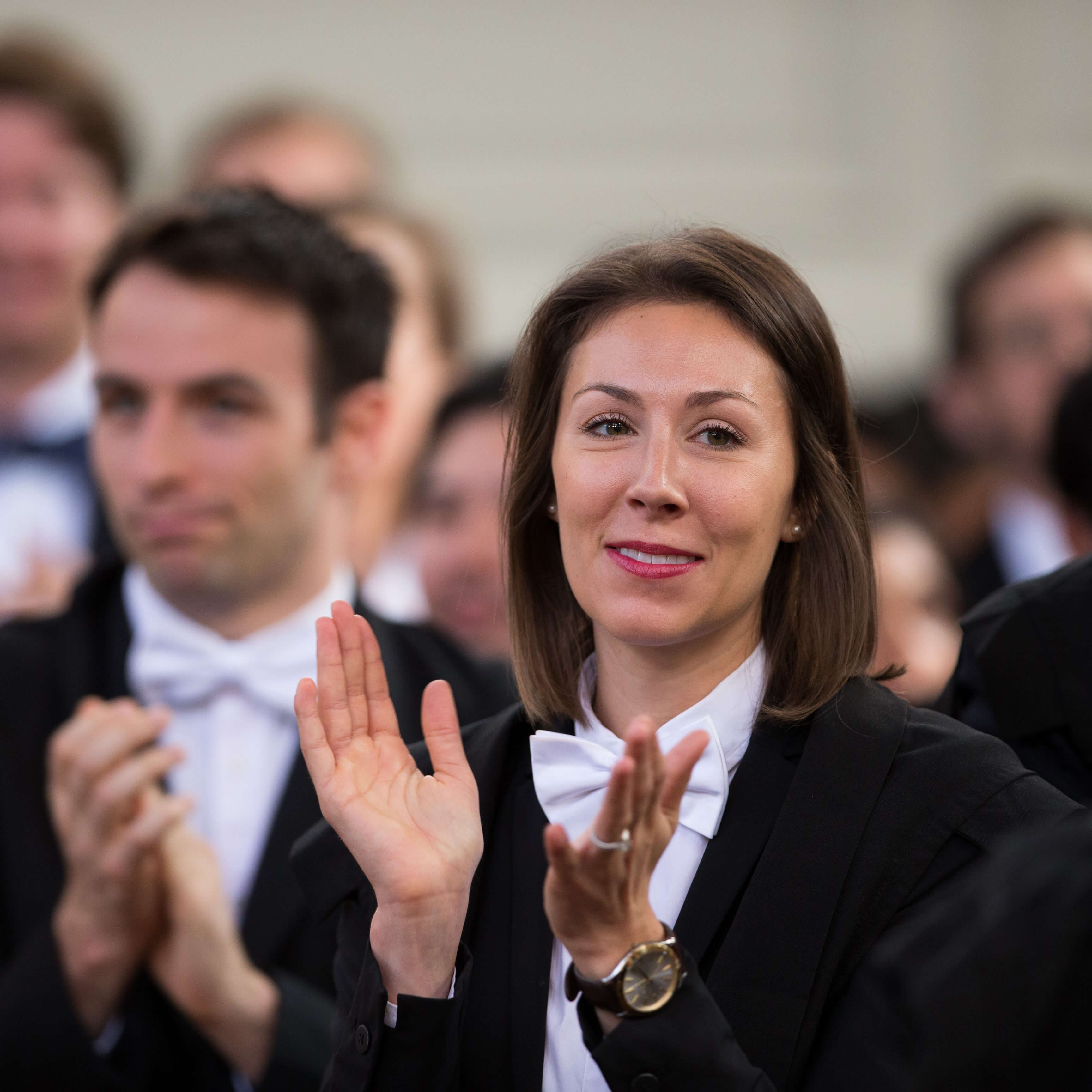 Woman clapping at graduation ceremony